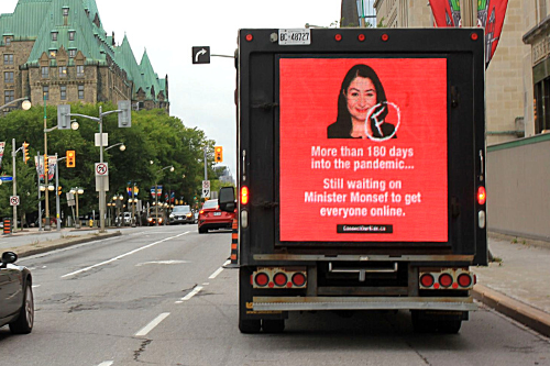 Truck with billboard: More than 180 days into the pandemic... Still waiting on Minister Monsef to get everyone online.